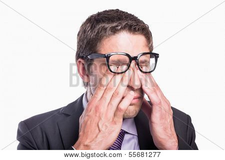 Close-up of a young worried businessman rubbing eyes against white background