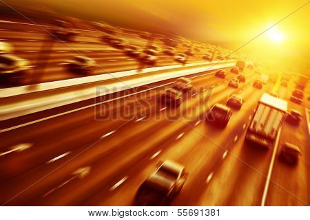 Cars in motion blur on highway during sunset.