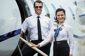 Portrait of happy confident airhostess and pilot standing on private jet's ladder poster