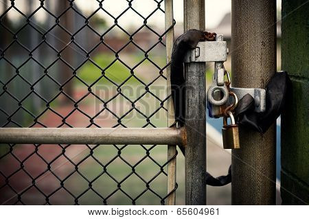 Closeup of a locked padlock securing a metal chain-link gate. poster