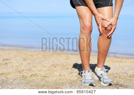 Running injury - Man jogging with knee pain. Close-up view of runner injured jogging on the beach clutching his knee in pain. Male fitness athlete.