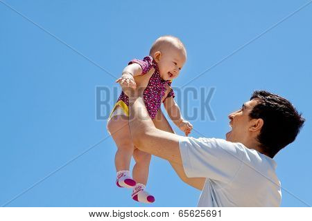Dad Lifting Baby Girl High In The Sky