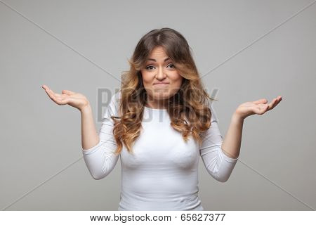 Shrugging woman in doubt doing shrug on grey background
