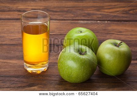 Glass of apple juice and green apples on wooden background