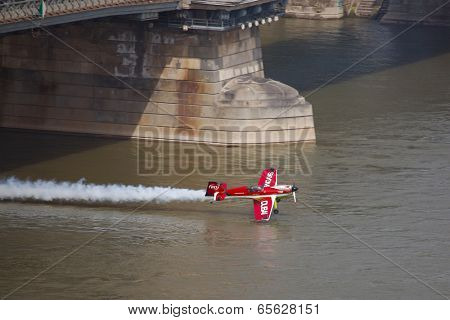 BUDAPEST, HUNGARY - MAY 1: Zoltan Veres fly under the Chainbridge as part of the May 1 celebration of 2014. Zoltan Veres is an European champion and Guiness record holder aerobatics pilot.