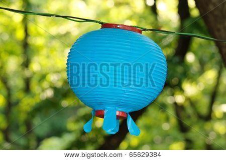 Blue round lantern on blurry floral green background