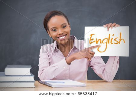 Happy teacher holding page showing english in her classroom at school