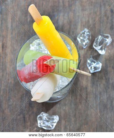 fruit ice pops on old wood background