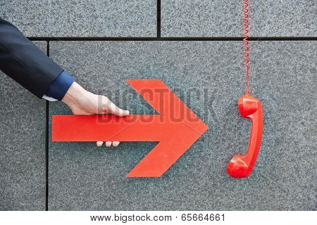 Hand pointing with big red arrow to a hanging phone