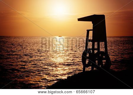 Lifeguard tower silhouette against sunrise over the Red Sea, Sharm el Sheik, Egypt.