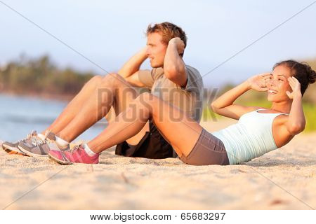 Situps training - young mixed race couple on beach sand in sunset happy smiling working out doing fitness crunches. Beautiful asian female and young caucasian fitness model