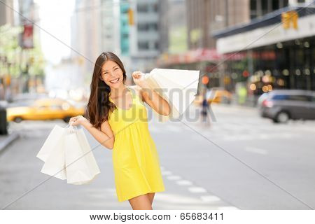 Urban shopping woman in New York City street with yellow taxi cab. Beautiful happy summer shopper holding shopping bags walking outside smiling. Multiracial Asian Caucasian model on Manhattan, USA.