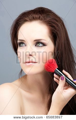 Portrait of the beautiful woman with bright makeup brushes near face, on grey studio background