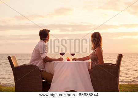 Couple sharing romantic sunset dinner on the beach
