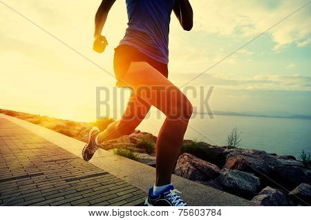 Runner athlete running at seaside. woman fitness jogging workout wellness concept.