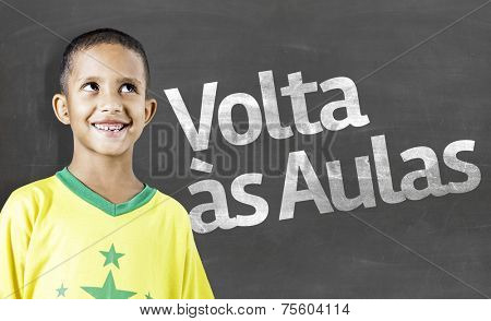 Cheerful smiling little kid (boy) against chalkboard. School concept. Back to School (In Portuguese: Volta as Aulas)