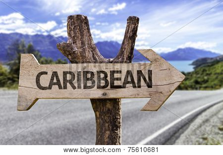 Caribbean wooden sign with a highway on background