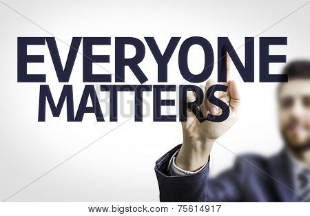 Business man pointing to transparent board with text: Everyone Matters