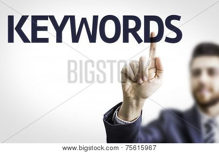 Business man pointing to transparent board with text: Keywords