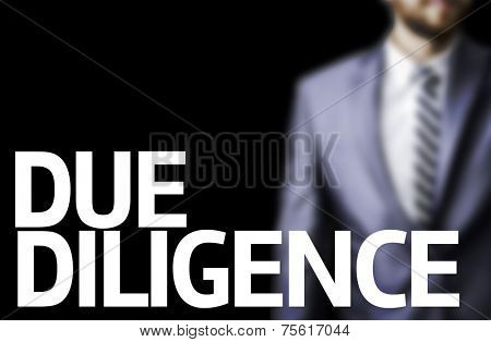 Due Diligence written on a board with a business man on background