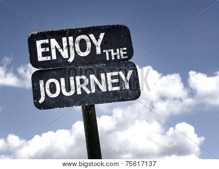 Enjoy The Journey sign with clouds and sky background