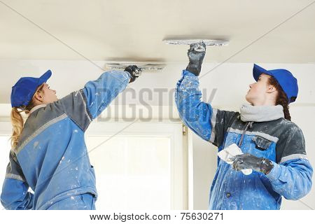 female plasterer painter at indoor ceiling renovation decoration stopping with spatula and plaster