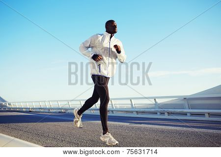 Attractive fit man running fast over beautiful road at sunset poster