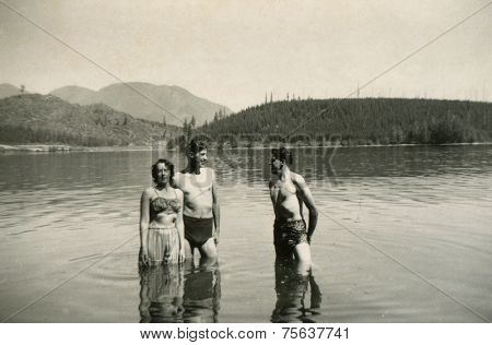 CANADA - CIRCA 1940s: Vintage photo shows two guys and devshki swimming in the river.