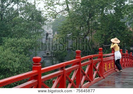 Woman visitor stroll and relax on the red bridge.