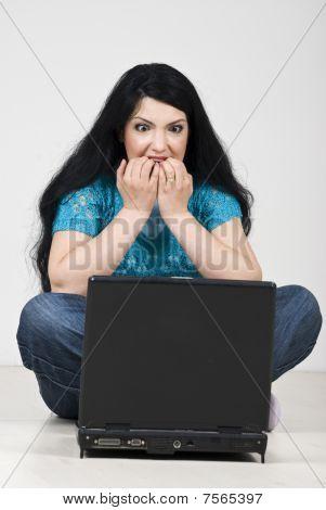 betonte Frau mit Laptop beißen ihre Nägel