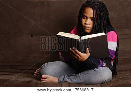 child reading book sitting on couch