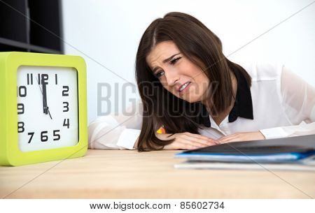 Tired businesswoman sitting at the table and looking on the clock