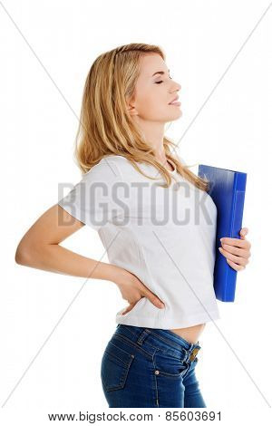 Side view of woman with back pain holding a binder. poster