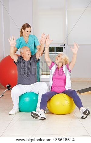 Two senior citizens doing sports in physiotherapy during rehab