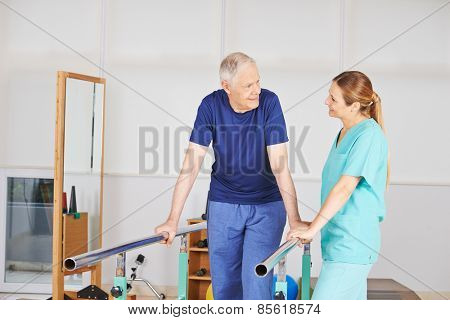 Old man at physiotherapy on a treadmill with physiotherapist