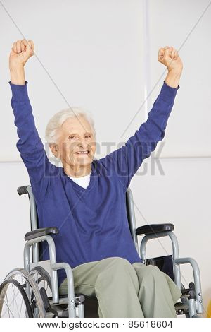 Old senior woman in wheelchair cheering with her arms up