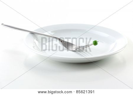 Pea on fork on plate isolated on white
