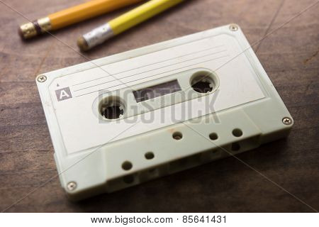 Early 70's cassette tape isolated with 70's pencil on grungy old desk with incoming light. Shallow depth of field.