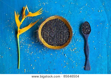 Handmade Coconut Bowl And Spoon With Shuck, Tea Leaves On Blue Wooden Background