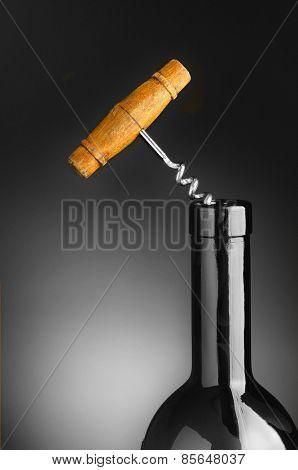 Old cork screw in blue wine bottle over a gray light to dark background.