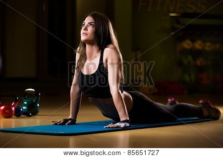 Attractive female athlete stretching on yoga mat in gym.Young and athletic girl in a gym
