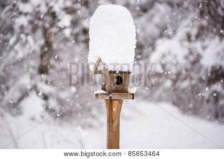Wooden bird feeder with a tall cap of snow standing in a winter garden with snow-covered trees and falling snowflakes in a winter season or weather concept. poster