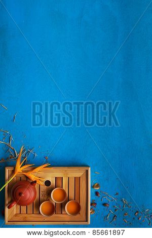 Clay Teapot, Three Teacups And Yellow Flower With Shuck On Blue Wooden Background.