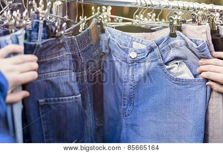 Close Up Of  Hands, Looking For Pants, Jeans On A Flea Market