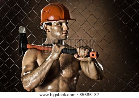 poster of the muscular tired worker chopper man in safety helmet with big heavy ax in hands on netting fence background