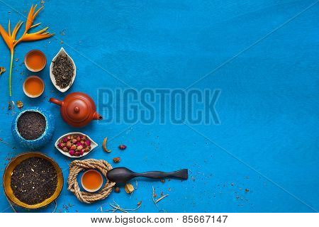 Clay Teapot, Three Teacups With The Rope, Rose Buds And Shuck On Blue Wodden Background.