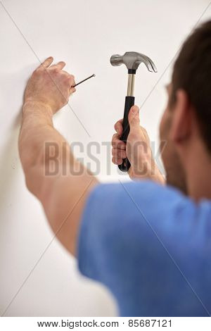 reapir, building, people and home renovation concept - close up of man with hammer hammering nail in wall