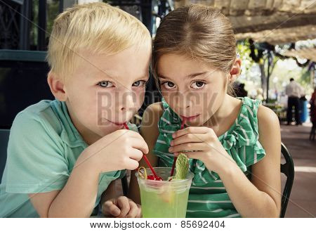 Cute kids sharing a mint julep drink at a cafe