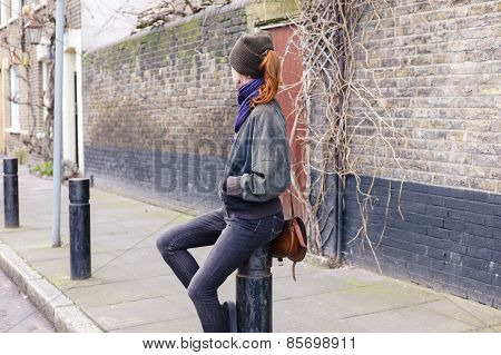 Woman Sitting On A Bollard In The Street