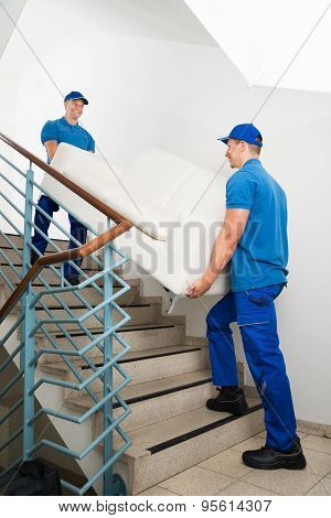 Two Male Movers Carrying Sofa On Staircase